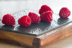 Close-up of raspberries. Soft focus of raspberries on kitchen board dark background with water drops Stock Images