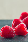 Close-up of raspberries. Soft focus of raspberries on kitchen board dark background with water drops Royalty Free Stock Photos