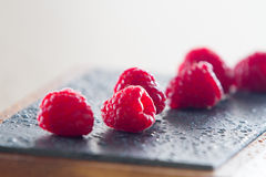 Close-up of raspberries. Soft focus of raspberries on kitchen board dark background with water drops Royalty Free Stock Image