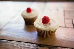 Close up of raspberry cupcakes on wooden table Stock Images