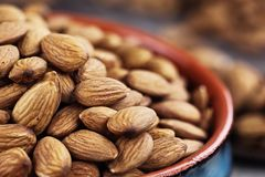 Close up of Raw Almonds. Close up of raw whole almonds in bowl and wooden spoon against a rustic background Royalty Free Stock Photography