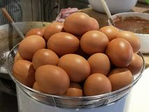 Close up of raw chicken eggs in a stainless basket. stock photography