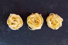 Close up of a raw dry italian pasta fettuccine on black chalkboa Royalty Free Stock Photo