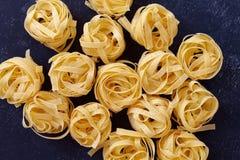 Close up of a raw dry italian pasta fettuccine on black chalkboa Stock Photo