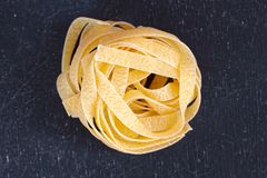 Close up of a raw dry italian pasta fettuccine on black chalkboa Stock Image