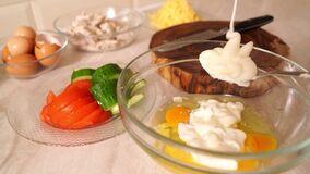 Close-up. in raw eggs add sour cream or mayonnaise to prepare dough for pizza.