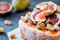 Close up of raw French soft cheese from Brittany region covered with chopped figs, walnuts and honey Stock Image