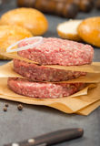 Close up raw ground beef meat cutlets with onion ring. On a stone surface Stock Image