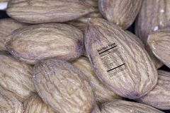 Almond with nutrition label. Close up of raw natural whole almond nuts with nutrition fact label Royalty Free Stock Photos