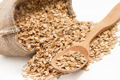 Close up raw oatmeal in wooden spoon and sack on white background Royalty Free Stock Image