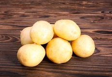 Close up of raw and organic new light brown potatoes on a dark brown wooden table. Summer harvest potato. A heap of baby potatoes. Royalty Free Stock Photos