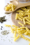 Close up raw pasta. With spices on kitchen background Stock Photos