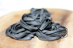 Close up of raw pasta, Black Squid ink fettuccine Stock Image