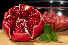 Close up of raw pomegranate opened on a wooden board with mnt and bawl of seeds. Juicy antioxidant fruit royalty free stock image