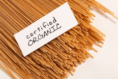 Close Up Of Raw Spaghetti. Uncooked whole wheat spaghetti with a certified organic sign Stock Images