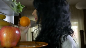 Close-up of raw vegan woman having a healthy lifestyle opening refrigerator and choosing fresh fruit on plate for eating. Closeup of raw vegan woman having a stock footage