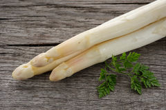 Close-up raw and white asparagus spears. With green chervil Stock Photo