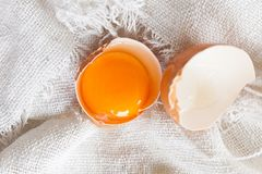Close up of raw yolk in eggshell on white linen background. Nnn stock images