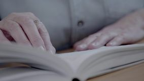 Close-up of reading a book and flipping pages. Hands of a senior stock video