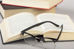 Close up of reading glasses laying on a book. Close up of a pair of reading glasses laying on an open book royalty free stock images