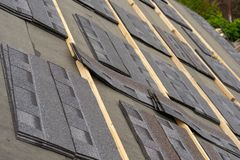 Asphalt tile roof on new house under construction stock photography
