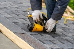 Workman using pneumatic nail gun install tile on roof of new house under construction royalty free stock image