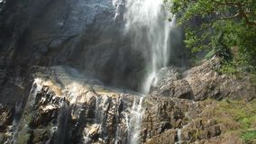 Close up real-time view of the beautiful waterfall. Close up real-time view panning down the rocky stepped cliff of the beautiful waterfall. Sri lanka stock footage