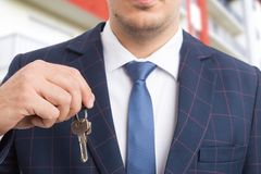 Close-up of realtor or real estate agent holding keys. As accommodation housing offer concept on apartment building background Stock Photos
