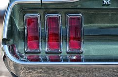 Close up, rear tail lights, Ford Mustang. Brooklands, Surrey. Close up capture of the rear tail lights of a Ford Mustang. , American classic car day, Brooklands royalty free stock photo