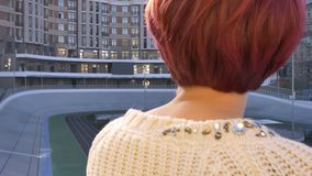 Close-up rear-view portrait of young pink-haired girl standing near railing and thoughtfully watching on sport arena. Close-up rear-view portrait of young pink stock footage