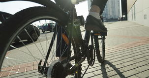 Close-up. Rear wheel of a bicycle. A businessman in blue pants and white socks is turning the pedals of a black bike stock footage