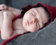Close up recém-nascido do bebê em um tampão vermelho Retrato do close-up de um beauti fotografia de stock