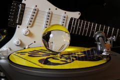 Close up of record player with yellow punk vinyl LP and crystal sphere glass ball und blurred electric guitar with black stock photo