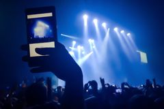 Close up of recording video with smartphone during a concert. Crowd at concert and blurred stage lights stock photo
