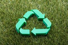 Close-up Of Recycle Symbol. On Green Grass stock photo