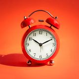 Close up red alarm clock on red background. Timing concepts royalty free stock photos