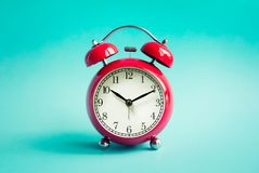 Close up red alarm clock on blue pastel background. Timing concepts royalty free stock photography