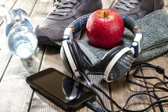 Healthy eating and equipment for leisure and outdoor sports, on rustic wooden background. Close-up of a red apple, sport shoes, audio headphone, smartphone Royalty Free Stock Images