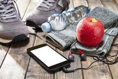 Healthy eating and equipment for leisure and outdoor sports, on rustic wooden background. Close-up of a red apple, sport shoes, audio headphone, smartphone Stock Photography