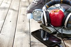 Healthy eating and equipment for leisure and outdoor sports, on rustic wooden background. Close-up of a red apple, sport shoes, audio headphone, smartphone Royalty Free Stock Image
