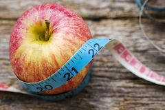 Red apple with measuring tape on wooden table Stock Image