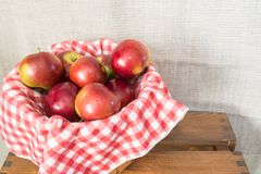 Close up of a basket of apples on a red and white checkered cloth Stock Image