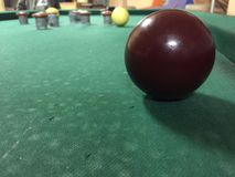 Close up of a red ball at a billards game. With the taps and white balls in the background Royalty Free Stock Image
