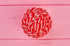 Close up red ball of woollen threads. Red ball of yarn for knitting on pink wooden background Royalty Free Stock Photography
