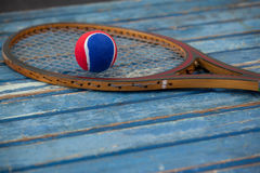 Close up of red and blue ball on wooden tennis racket Stock Photos