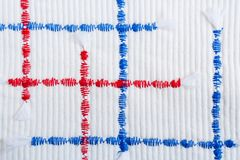 Close-up red and blue textural zigzag seams on relief white fabric. Close-up randomly arranged vertical and horizontal red and blue textural  zigzag seams on Royalty Free Stock Photos
