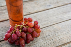 Close-up of red bunch of grapes with bottle of red wine. On wooden table stock photo