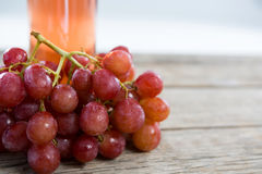 Close-up of red bunch of grapes with bottle of red wine. On wooden table royalty free stock image