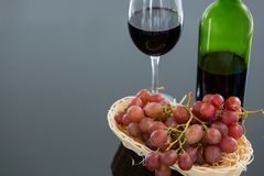 Close-up of red bunch of grapes with glass and bottle of red wine. Against grey background royalty free stock photos