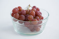 Close-up of red bunch of grapes in glass bowl. On white background royalty free stock photo